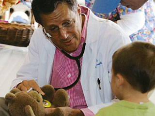 Dr. Stark examining a teddy bear with a little boy